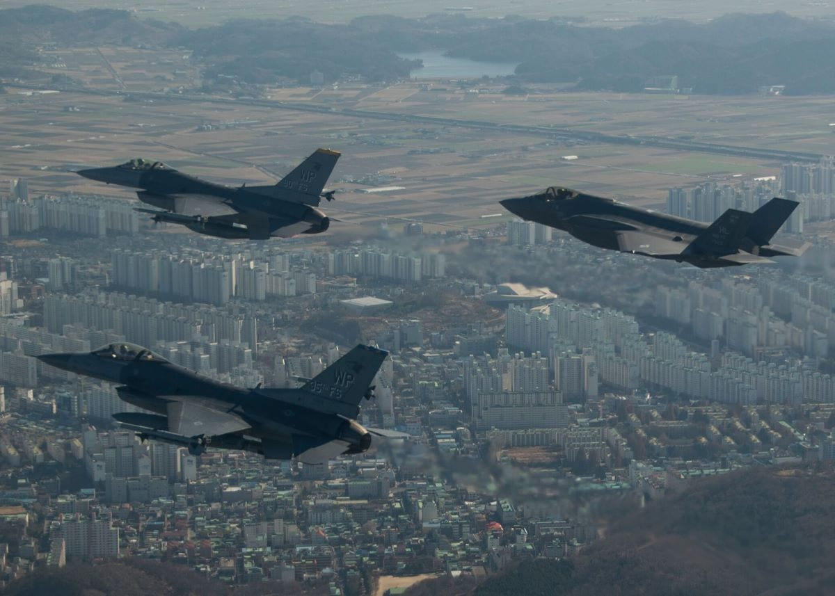 A U.S. Air Force F-35A Lightning II assigned to Hill Air Force Base, Utah, conducts a training flight with F-16 Fighting Falcons assigned to Kunsan Air Base, Republic of Korea, over the city of Gunsan, ROK, Dec. 1, 2017. The Air Force Research Laboratory is looking into pairing unmanned older generation fighters such as the F-16 with fifth- generation fighters like the F-35.