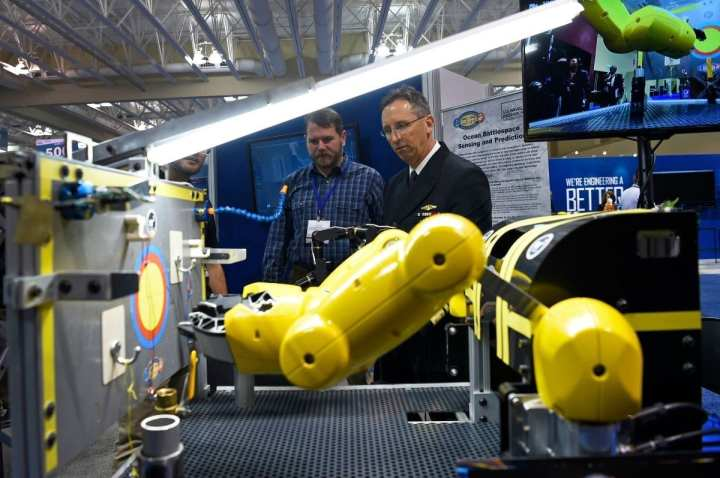 Rear Adm. David Hahn operates the Maritime Dexterous Manipulation System (MDMS) from RE2 Robotics while visiting the Office of Naval Research exhibit during the 2018 OCEANS conference and exposition. The MDMS consists of two 5-degree-of- freedom robotic arms with two-finger grippers. The arms are electro-mechanical and are roughly the same size as a human, meaning that when mounted on a smaller underwater vehicle, they can perform human-like tasks.