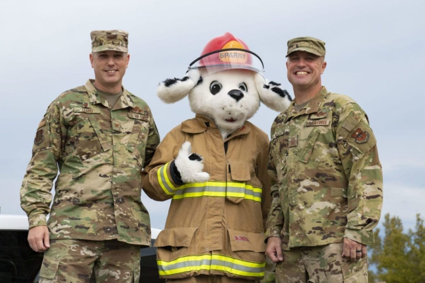 U.S. Air Force Col. Matthew Leard, 97th Air Mobility Wing commander, left, and U.S. Air Force Chief Master Sgt. Randy Kay III, 97th AMW command chief, pose for a photo with Sparky, the 97th Civil Engineer Squadron firedog, at the start of the Fire Prevention week parade, Sept. 28, 2019, at Altus Air Force Base, Okla. (U.S. Air Force photo by Airman 1st Class Breanna Klemm)