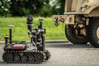 RoMan, short for Robotic Manipulator, is a tracked robot with arms and hands -- necessary appendages to remove heavy objects and other road debris from military vehicles' paths. (Photo Credit: David McNally)