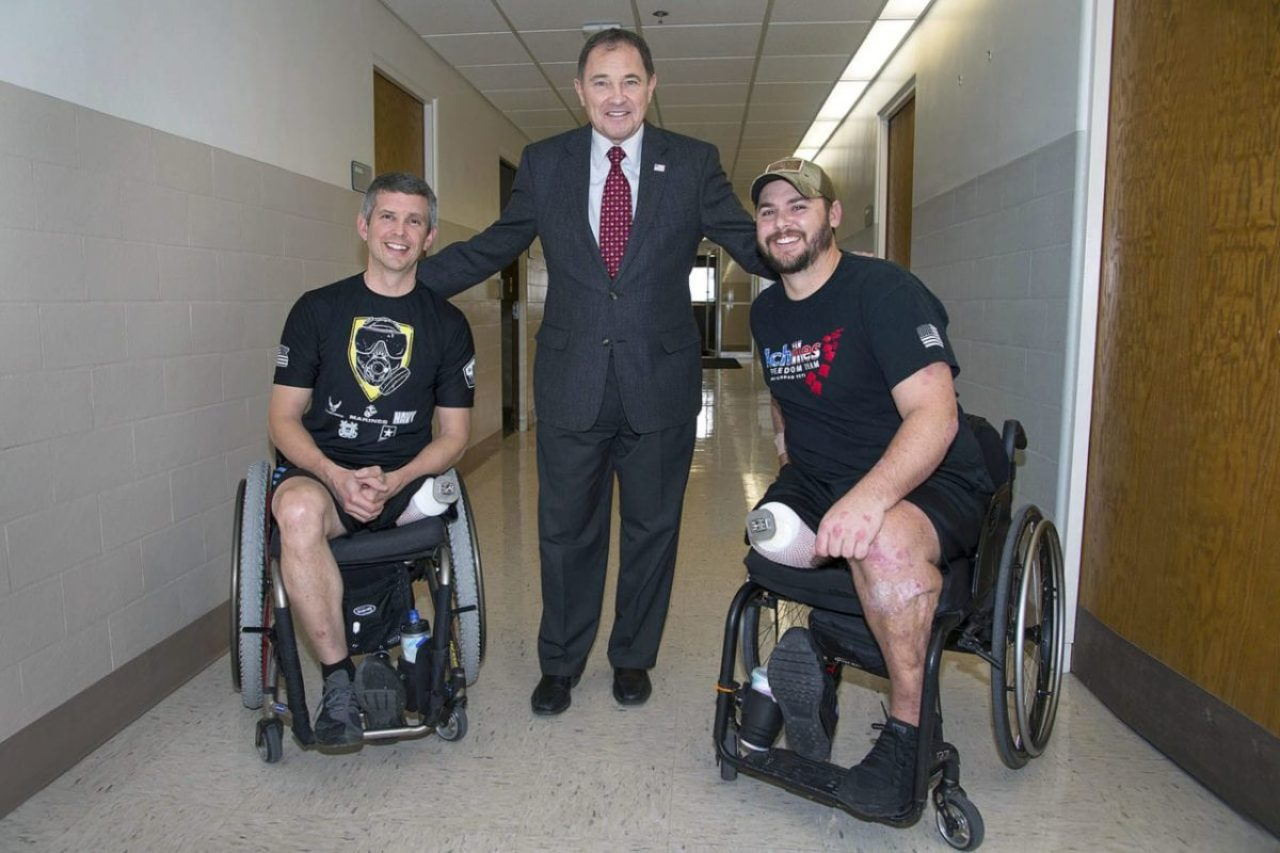 Utah Gov. Gary Herbert meets with Enduring Freedom and Iraqi Freedom meets with Enduring Freedom and Iraqi Freedom veterans Ed Salau, left, and Bryant Jacobs, right in February 2016. at the VA Salt Lake City Health Care System. In December 2015, Salau and Jacobs became the first Americans to undergo surgery - part of an FDA- approved study - to receive percutaneous osseointegrated prostheses (POPs), titanium implants in their residual limbs to which prostheitc limbs attach.