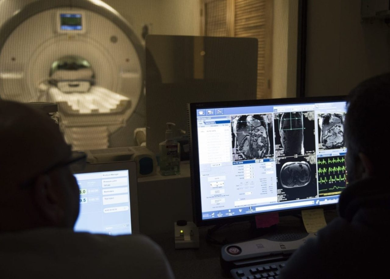 Cardiac magnetic resonance imaging technologies observe a patient during a cardiac MRI scan at Wilford Hall Ambulatory Surgical Center, Joint Base San Antionio- Lackland, Texas. Cardiac MRI is noninvasive, takes approximately 20-45 minutes, and enables an assessment of the function and structure of the heart.
