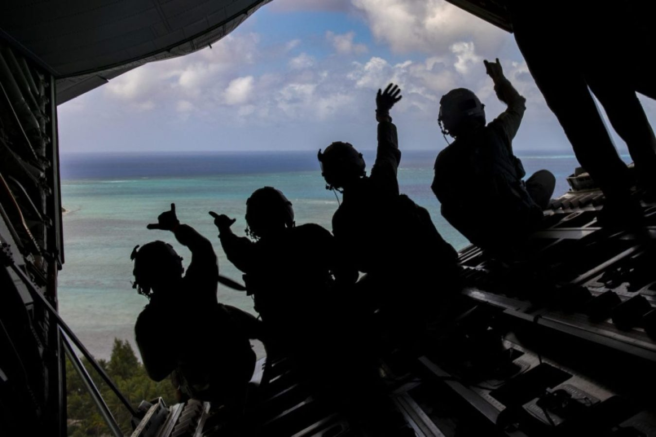 Loadmasters with the 36th Airlift Squadron out of Yokota Air Base, Japan wave to the villagers on the island of Norwin, Federated States of Micronesia, after delivering four Low-Cost, Low Altitude humanitarian assistance bundles during Operations Christmas Drop, Dec. 13, 2019. ( U.S. Air Force photo by Senior Airman Matthew Gilmore)