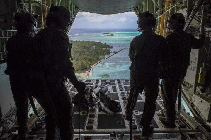 Loadmasters with the 36th Airlift Squadron out of Yokota Air Base, Japan, watch as the four Low-Cost, Low-Altitude humanitarian assistance bundles they just airdropped parachute down to those in need during Operation Christmas Drop 2019, at Nomwin, Federated States of Micronesia, Dec. 13, 2019 (U.S. Air Force photo by Senior Airman Matthew Gilmore)