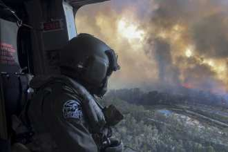 Royal Australian Navy Aircrewman, Petty Officer Jason Wickman assesses the Grose Valley bushfire in the Blue Mountains National Park during a sortie on an 808 Squadron MRH90 Taipan Military Support Helicopter.