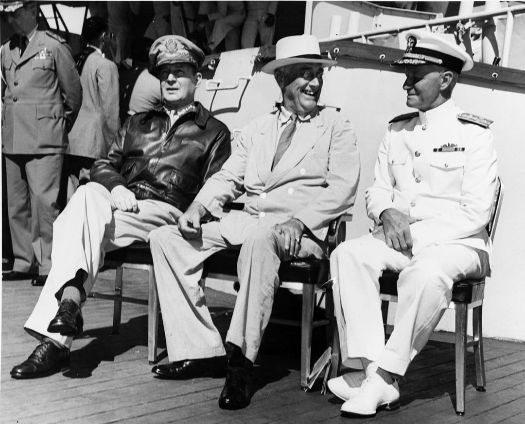 Gen. Douglas MacArthur, President Franklin D. Roosevelt, and Adm. Chester W. Nimitz on board USS Baltimore (CA 68), at Pearl Harbor, Hawaii, July 26, 1944. While Roosevelt was determined to achieve the unconditional surrender of the Japanese, MacArthur and Nimitz differed on how to achieve that outcome.