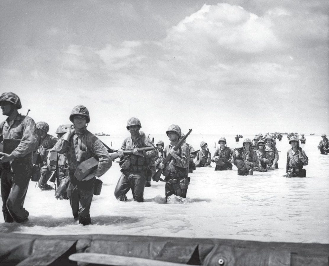 Despite enemy fire, Marines wade toward shore at Tarawa Island. Landing boats and barges brought them to within 500 yards of the beach, but the coral bottom prevented the boats coming any closer to the shore. LVTs were able to cross the reef and deliver Marines and supplies to the shore, but there were too few and most were knocked out. Casualties were heavy. U.S. Naval History and Heritage Command Photo