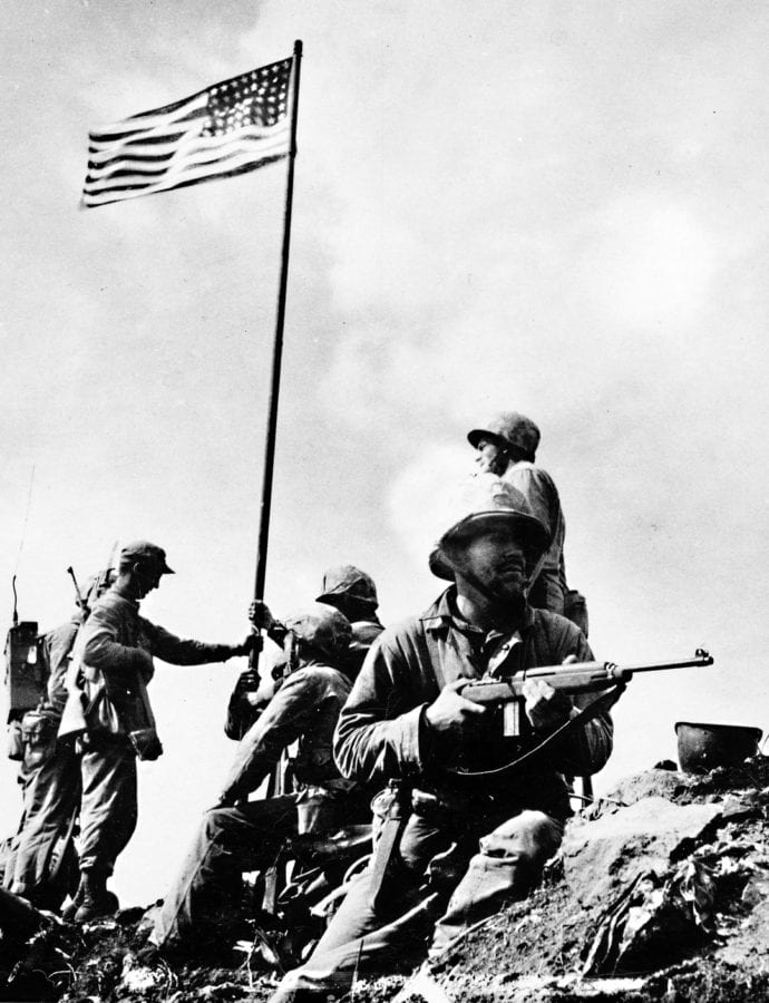 """Pictured during the first flag-raising on Mount Suribachi are, left to right, 1st Lt. Harold Schrier (kneeling behind radioman's legs); Pfc. Raymond Jacobs (radioman reassigned from F Company); Sgt. Henry """"Hank"""" Hansen (wearing cap, holding flagstaff with left hand); Platoon Sgt. Ernest """"Boots"""" Thomas (seated); Pvt. Phil Ward (holding lower flagstaff with his right hand); PhM2c John Bradley, USN; Pfc. James Michels (holding M1 carbine); and Cpl. Charles W. Lindberg (standing above Michels). U.S. MARINE CORPS BY SSGT. LOUIS R. LOWERY"""