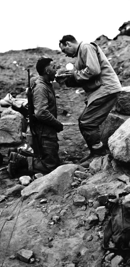 Father Joseph Hammond gives Holy Communion to a 4th Division Marine on Iwo Jima, Feb. 27. 1945, even as the battle rages on. MARINE CORPS HISTORICAL CENTER PHOTO