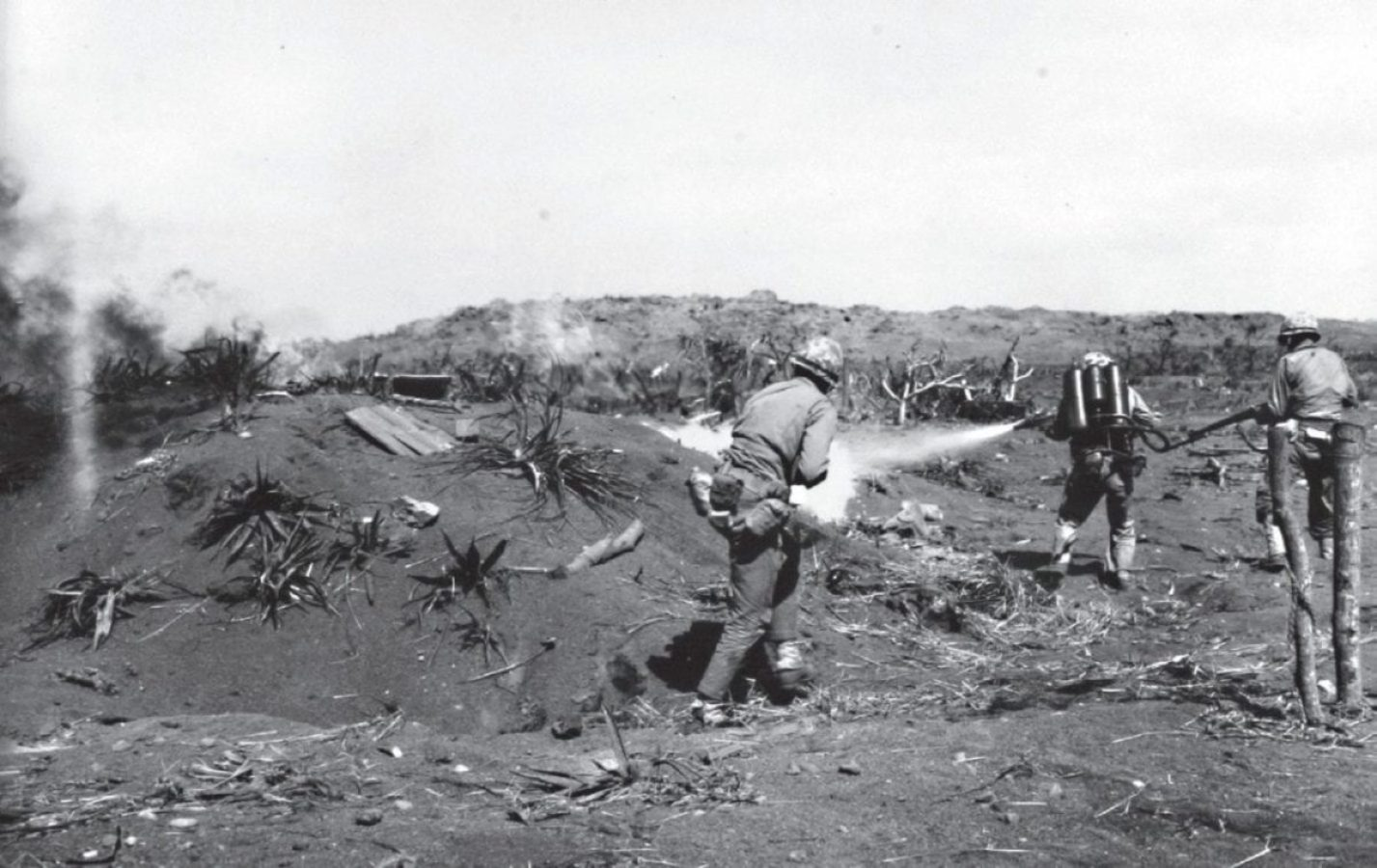A Marine flamethrower team silences an enemy dugout on Iwo Jima. While two riflemen cover the entrance, the flamethrower showers the position with liquid flame. U.S. MARINE CORPS HISTORICAL CENTER