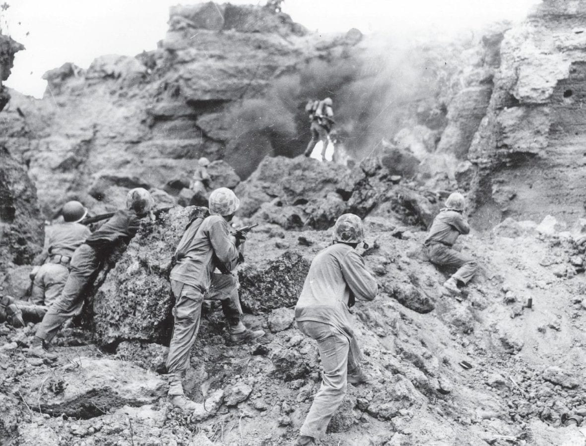 Covered by Marine riflemen in the foreground, a Marine flamethrower clears an enemy cave on the north side of the island. Persuasion was attempted first, but as was the case with most of the Japanese soldiers, surrender was not an option. U.S. MARINE CORPS HISTORICAL CENTER