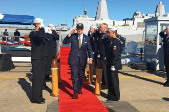 Sen. Tom Carper renders a salute as he is welcomed to the change of command ceremony for Pre-Commissioning Unit (PCU) Delaware (SSN 791) at Naval Station Norfolk in Norfolk, Virginia, Nov. 8, 2019.