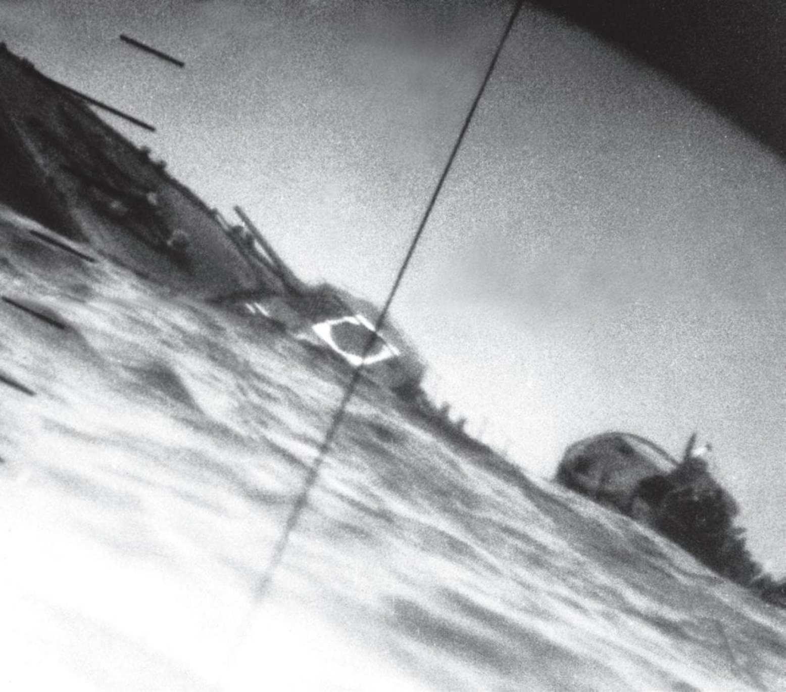 The torpedoed Japanese destroyer Yamakaze sinking on June 25, 1942, approximately 75 miles southwest of Yokahama Harbor, Japan, photographed through the periscope of the U.S. Navy submarine USS Nautilus (SS 168).