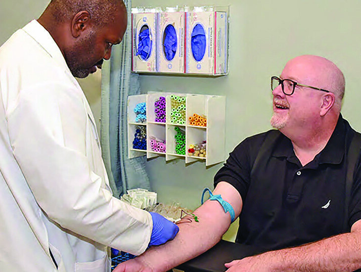 Joe Shanks, a medical technician at the San Francisco VA Medical Center, draws a blood sample from Air Force veteran Matt Parsons during enrollment in the Million Veteran Program (MVP).