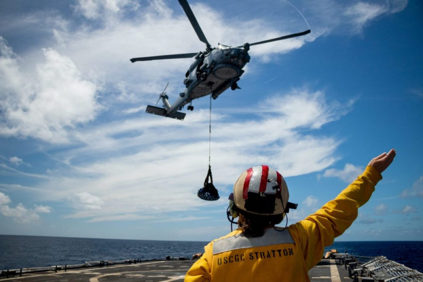 "A landing signal officer aboard the Coast Guard Cutter Stratton (WMSL 752) directs the aircrew aboard an MH-60R Seahawk, from the ""Easyriders"" of Helicopter Maritime Strike Squadron (HSM) 37 during a vertical replenishment while underway in the Eastern Pacific Ocean, June 5, 2020. Stratton is deployed to the U.S. Southern Command area of responsibility to support Joint Interagency Task Force South's mission, which includes counter illicit drug trafficking in the Caribbean and Eastern Pacific. (U.S. Coast Guard photo)"