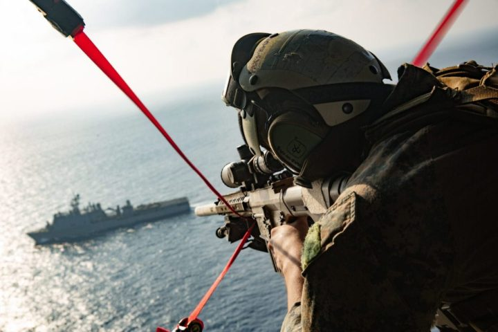 Cpl. Richard Simons IV, a reconnaissance marine with the Maritime Raid Force (MRF), 31st Marine Expeditionary Unit (MEU), provides aerial security during a Visit Board Search and Seizure (VBSS) mission on a UH-1Y Venom helicopter with Marine Medium Tiltrotor Squadron 262 (Reinforced), 31st MEU, after taking off from amphibious assault ship USS America (LHA 6). (U.S. Marine Corps photo by Cpl. Brandon Salas)