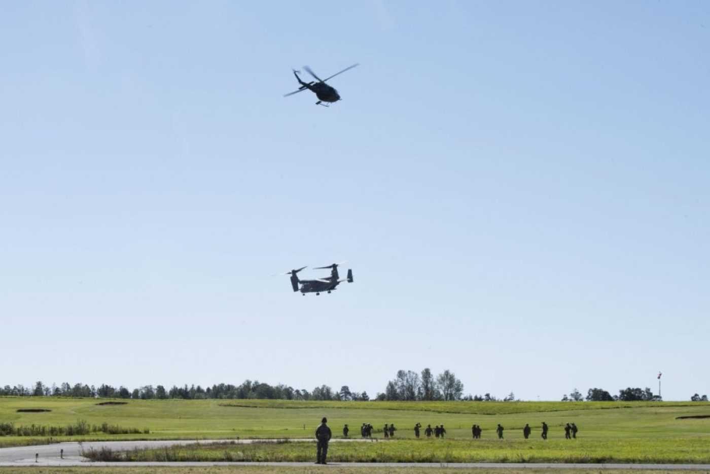 A Royal Norwegian Air Force Bell 412 Helicopter and a CV-22B Osprey, based out of RAF Milden-hall, U.K., hovers over 321st Special Tactics Squadron Airmen after performing fast-rope training at Rygge Air Station, Norway, August 25, 2020. Integration with the Norwegian Air Force allowed the 352d Special Operations Wing to enhance and strengthen bonds with our partner nation and further se-cure the strategic high-north region. The exercise provided training for 352d Special Operations Wing members on capabilities such as personnel recovery, forward area refueling point, aerial refueling, mari-time craft delivery system, and fast rope training. (U.S. Air Force photo by Staff Sgt. Michael Wash-burn)