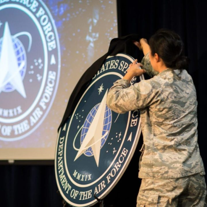 Airman unveils the new U.S. Space Force seal during the Space and Missile System Center's celebration marking the conclusion of SMC 2.0 to Full Operational Capability held in Gordon Conference Center, Los Angeles Air Force Base, Calif., Jan. 30, 2020. The celebration marks the completion of the largest transformation in SMC's 65-year history in which the center has eliminated layers of bureaucracy, flattened the organization and put key decision-makers closer to their programs to speed decision making and more rapidly deliver capabilities to the warfighter and the world. The Tenants of SMC 2.0 which are E.P.I.C. (Enterprise, Partnership, Innovation and Culture) Speed will continue in the newly re-architected structure. (U.S. Air Force photo by Photo Van De Ha)