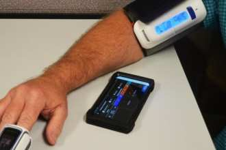 "A staff member demonstrates CRDAMC's ""virtual ward"" (pilot) system which includes a wireless blood pressure cuff and pulse oximeter that transmits a patient's vital-sign readings via Bluetooth to a web-based database on the dedicated cellphone. The remote monitoring capabilities of the Virtual Ward offers certain patients the option to reduce their hospital stay and recover at home. (Photo by Patricia Deal, CRDAMC.)"