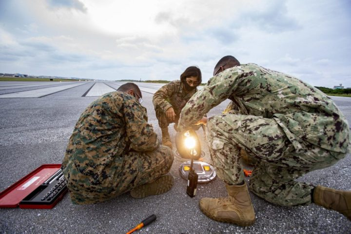 U.S. Marines with General Facilities (GF) and Navy Construction Electrician 2nd Class Ira Mozee, a native of Saint Lucie, Florida, repair threshold lights on the airfield during on-the-job training with Seabees, on Marine Corps Air Station Futenma, Okinawa, Japan, Dec. 3, 2020. When a service ticket is issued, GF Marines shadow Seabees to learn their side of the job. Seabees are trained to build and maintain permanent structures while Marines are trained in expedient construction and maintenance. The training is hands-on, teaching Marines how to build, plumb and power structures to code for long term use. (U.S. Marine Corps photo by Cpl. Karis Mattingly)