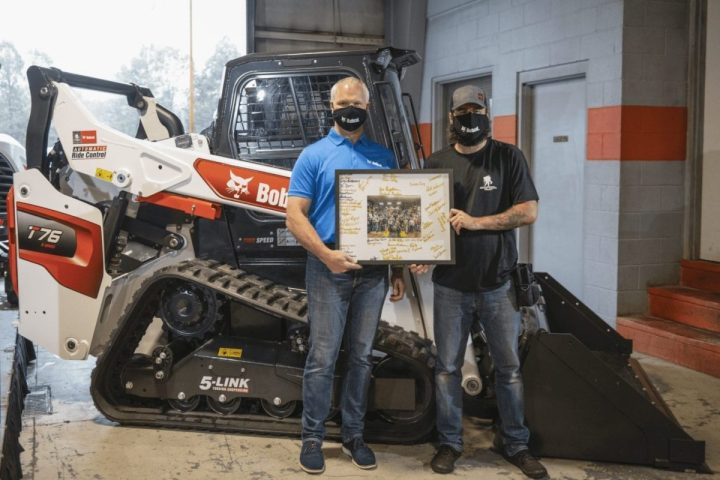 Andrew and Doosan Bobcat North America President Mike Ballweber. Ballweber traveled to Piedmont Bobcat to present Andrew with the loader and a photo of the Bobcat employees who built it.