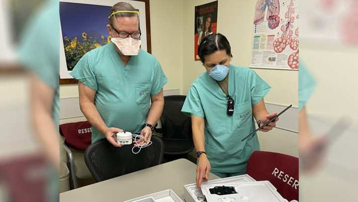 Mike Lavers, sleep technician, and Sgt. 1st Class Annabelyn Verdeflor, noncommissioned officer in charge of the Pulmonary Clinic, look over the components of a home healthcare kit as part of the COVID-19 Remote Monitoring Program, a joint effort of the Virtual Medical Center and Brooke Army Medical Center, Joint Base San Antonio-Fort Sam Houston, Dec. 16, 2020. (Photo by Elaine Sanchez, Brooke Army Medical Center.)