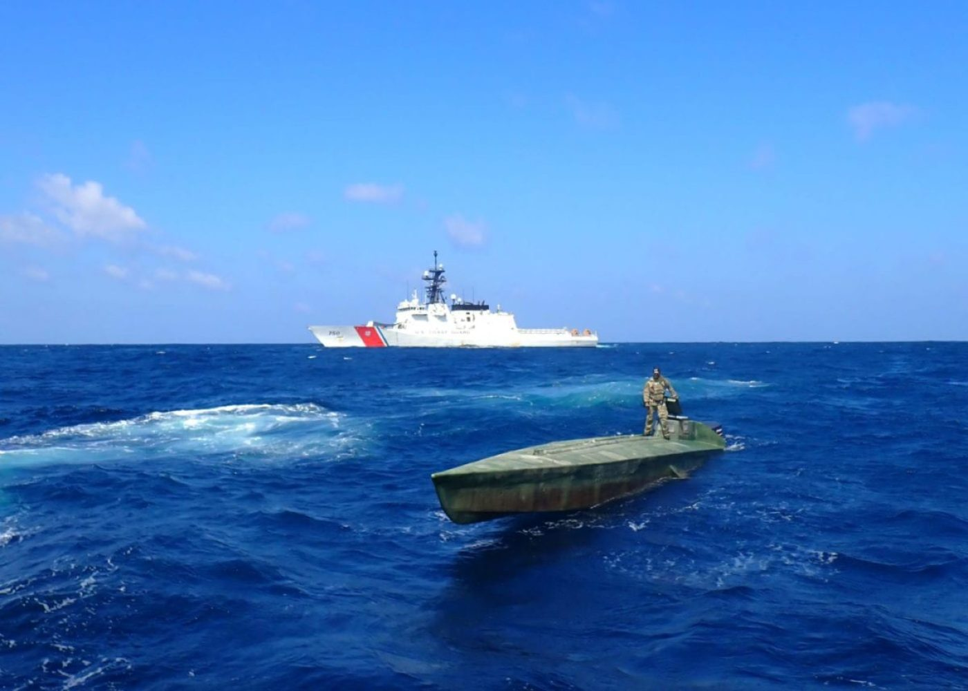 A Coast Guard Cutter Bertholf (WMSL 750) boarding team member stands atop an interdicted low-profile vessel in the Eastern Pacific Ocean, Feb. 1, 2021. Cartels design low-profile vessels specifically to evade law enforcement and to ferry large quantities of illicit contraband while riding low in the water. U.S. Coast Guard photo courtesy of the Coast Guard Cutter Bertholf.