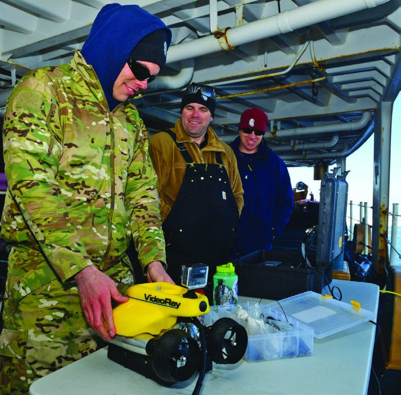 From left to right, Petty Officer 2nd Class Kyle McGann, a marine science technician, Petty Officer 2nd Class Bill Glenn, an electronics technician, and Chief Petty Officer Michael Perrault, a machinery technician, all members of the military dive team aboard the Coast Guard Cutter Polar Star, inspect a remotely operated vehicle (ROV) prior to launch in the Ross Sea, Jan. 11, 2015. Dive team members use ROVs to inspect vessels for underwater damage. (Coast Guard photo by Petty Officer 1st Class George Degener)