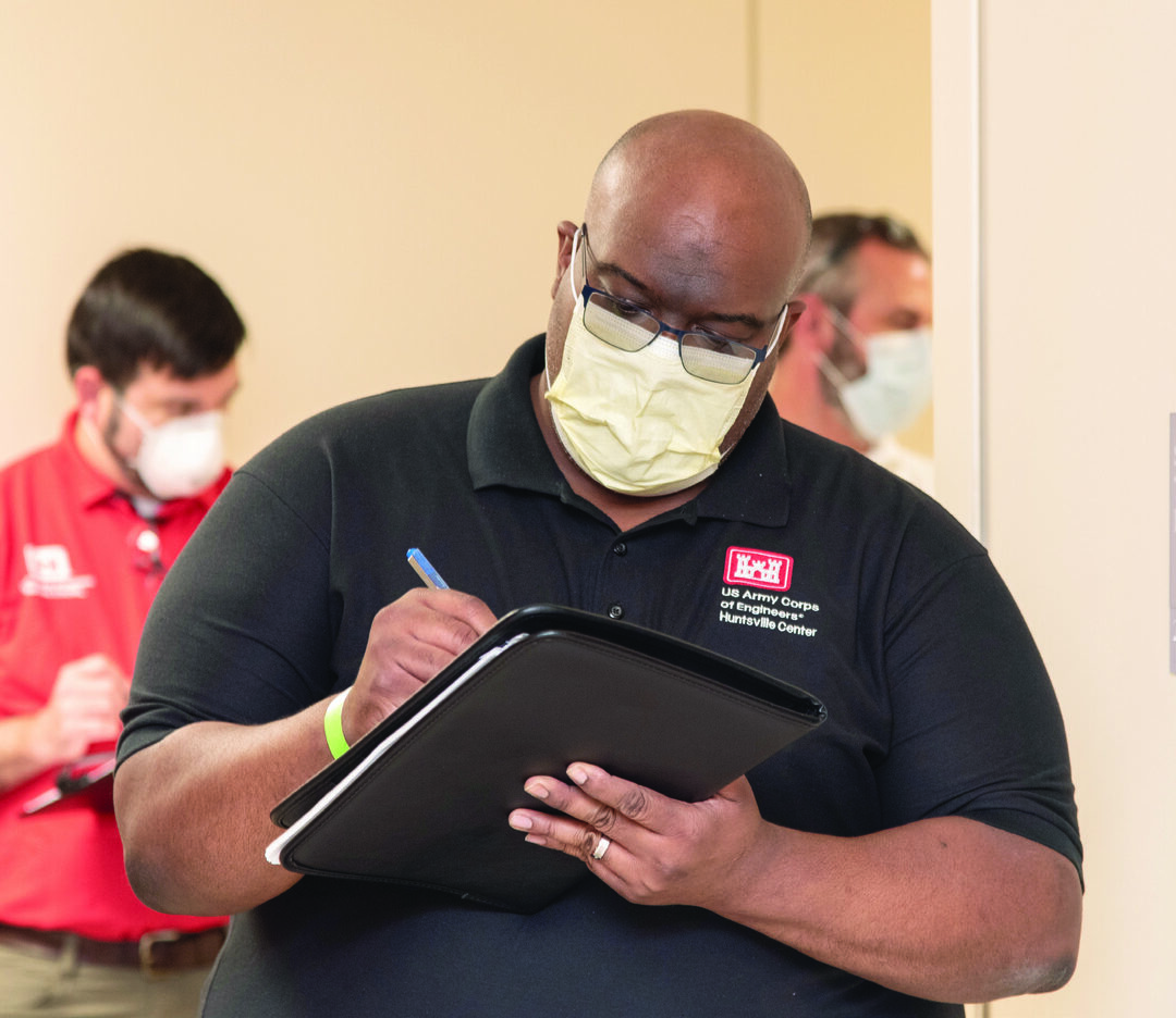 Jelani Ingram, acting Architecture Branch chief with the U.S. Army Engineering and Support Center, Huntsville, takes notes during a site assessment in Tuscaloosa, Alabama, April 6, 2020, with a group including hospital staff and administrators, as well as his colleagues from Huntsville Center and an engineer with the Mobile District. (Photo by Stephen Baack, U.S. Army Engineering and Support Center, Huntsville)