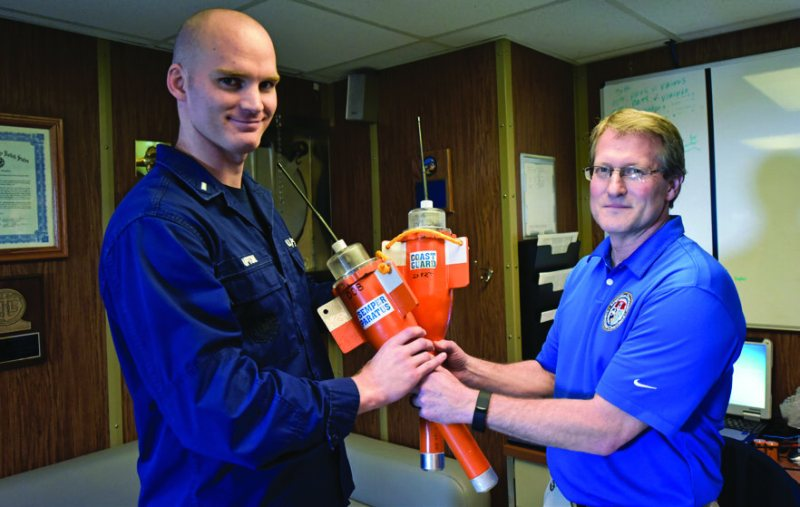 Lt. j.g. Jonathan Upton, operations officer, Coast Guard Cutter Aspen, receives two MOTT devices from Brian Dolph, Coast Guard Research and Development Center test lead, following a MOTT device demonstration in San Francisco, Jan. 17, 2018. (Coast Guard photo by Petty Officer 3rd Class Sarah Wilson)