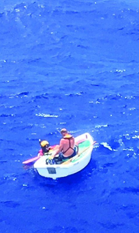 A rescue swimmer with Coast Guard Air Station Clearwater talks with and prepares the survivor of a sunken 36-foot sailing vessel to be hoisted, June 29, 2018, approximately 6 miles southwest of Big Sand Cay, Turks and Caicos. The Coast Guard 7th District Command Center received a 406 megahertz emergency position indicating radio beacon alert from the 36-foot sailing vessel Wings with one person aboard and rescued the mariner. U.S. COAST GUARD PHOTO COURTESY OF AIR STATION CLEARWATER