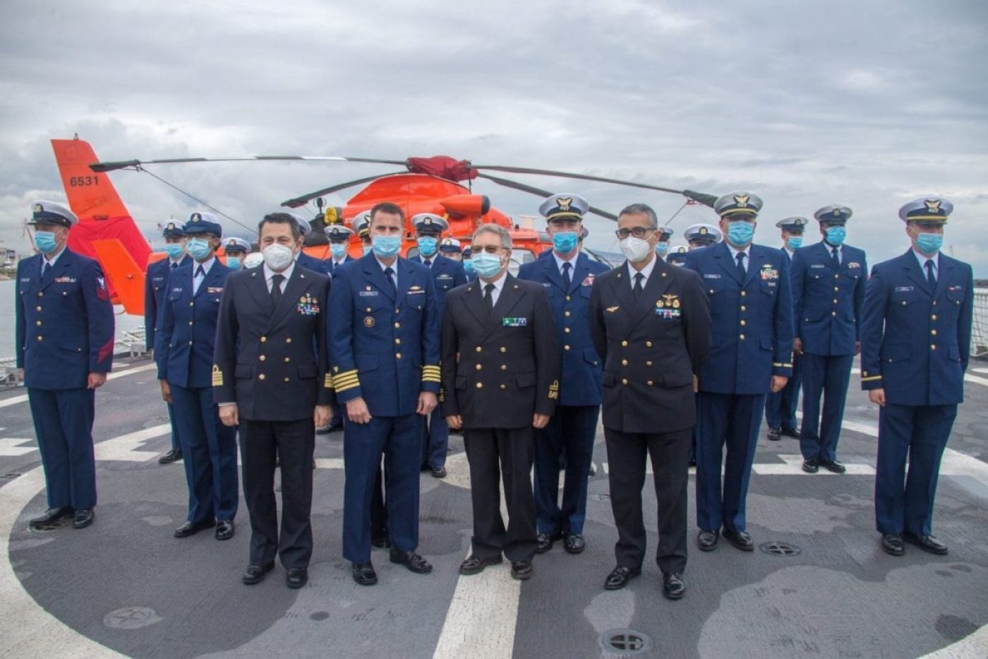 Members from the Italian Coast Guard and USCGC Hamilton (WMSL 753) pose for a photo in front of a U.S. Coast Guard MH-65 Dolphin helicopter aboard Hamilton, April 23, 2021. U.S. Coast Guard Cutter Hamilton is on a routine deployment in the U.S. Sixth Fleet area of operations in support of U.S. national interests and security in Europe and Africa. (U.S. Coast Guard photo)