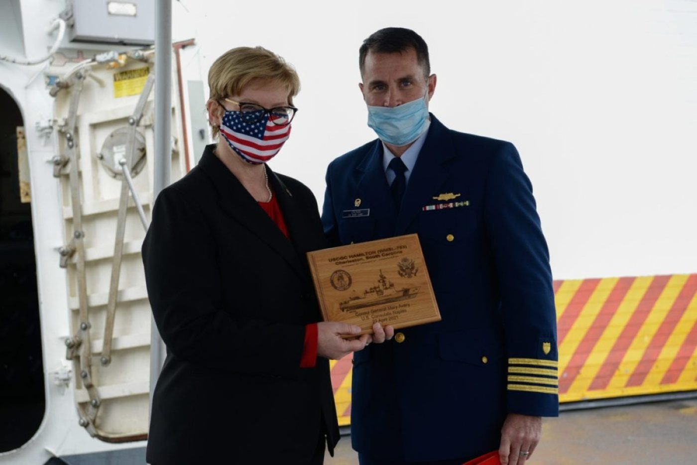 Consul General Mary Avery, U.S. Consulate Naples, and Capt. Timothy Cronin, commanding officer of USCGC Hamilton (WMSL 753) pose for a photo on the flight deck of Hamilton after Cronin presented Avery with a plaque, April 22, 2021. (U.S. Coast Guard photo by Petty Officer 3rd Class Sydney Phoenix)