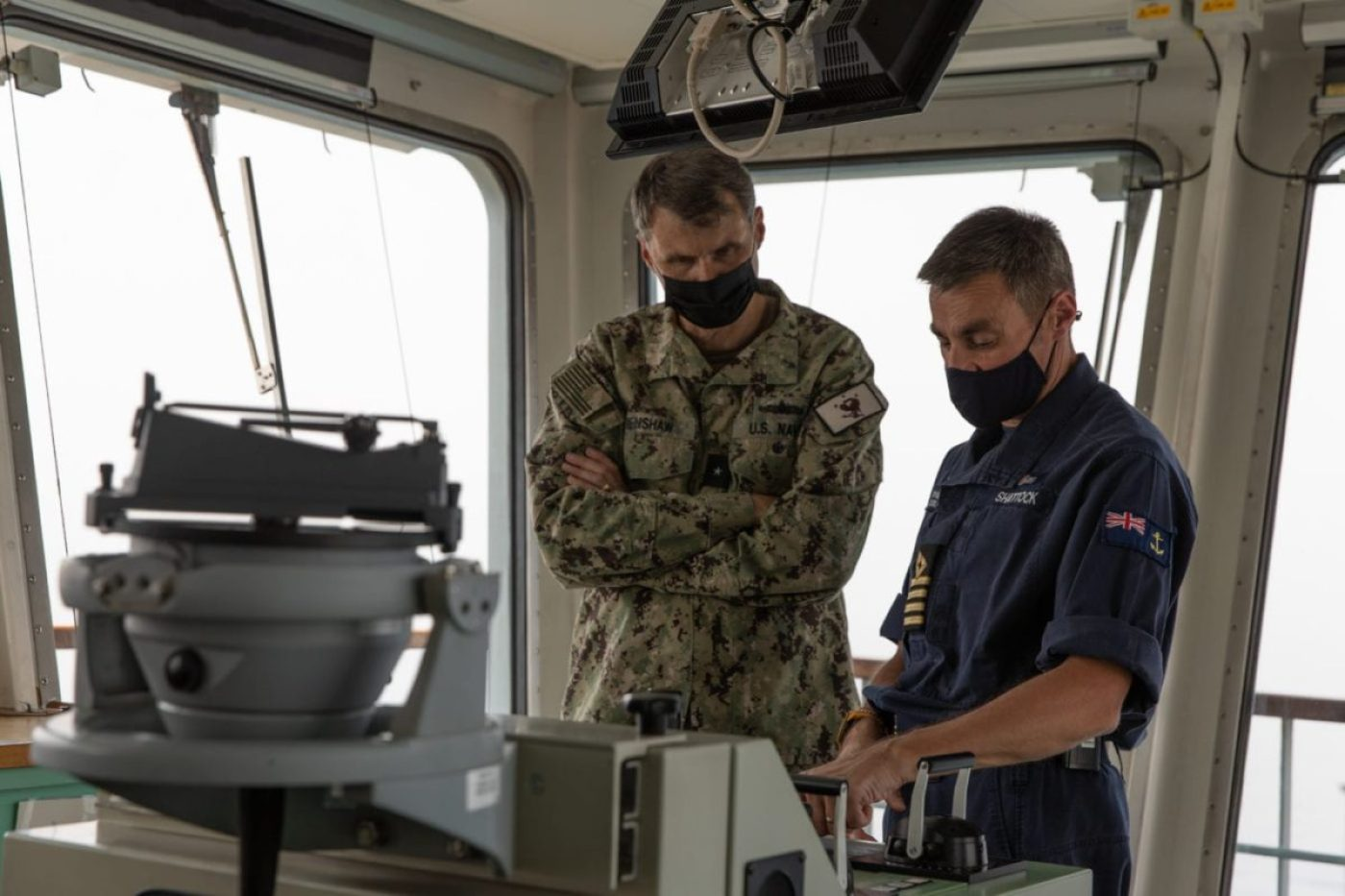 Royal Fleet Auxiliary Capt. Sam Shattock, commanding officer of Royal Fleet Auxiliary landing ship dock RFA Cardigan Bay (L 3009), right, and Rear Adm. Curt Renshaw, deputy commander of U.S. Naval Forces Central Command and U.S. 5th Fleet, discuss radar capabilities during exercise Artemis Trident 21. (U.S. Army photo by Sgt. Wheeler Brunschmid)