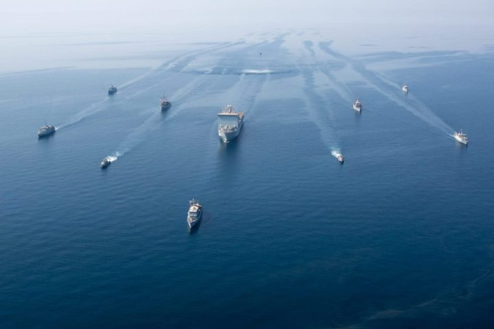 """A multinalional group of mine countermeasure ships from the French Marine Nationale, UK Royal Navy, U.S. Navy and a MH-53E Sea Dragon helicopter, attached to the """"Blackhawks"""" of Helicopter Mine Countermeasures Squadron (HM-15), operate in formation during exercise Artemis Trident 21 in the Arabian Gulf, April 21. (U.S. Army photo by Spc. Theoren Neal)"""