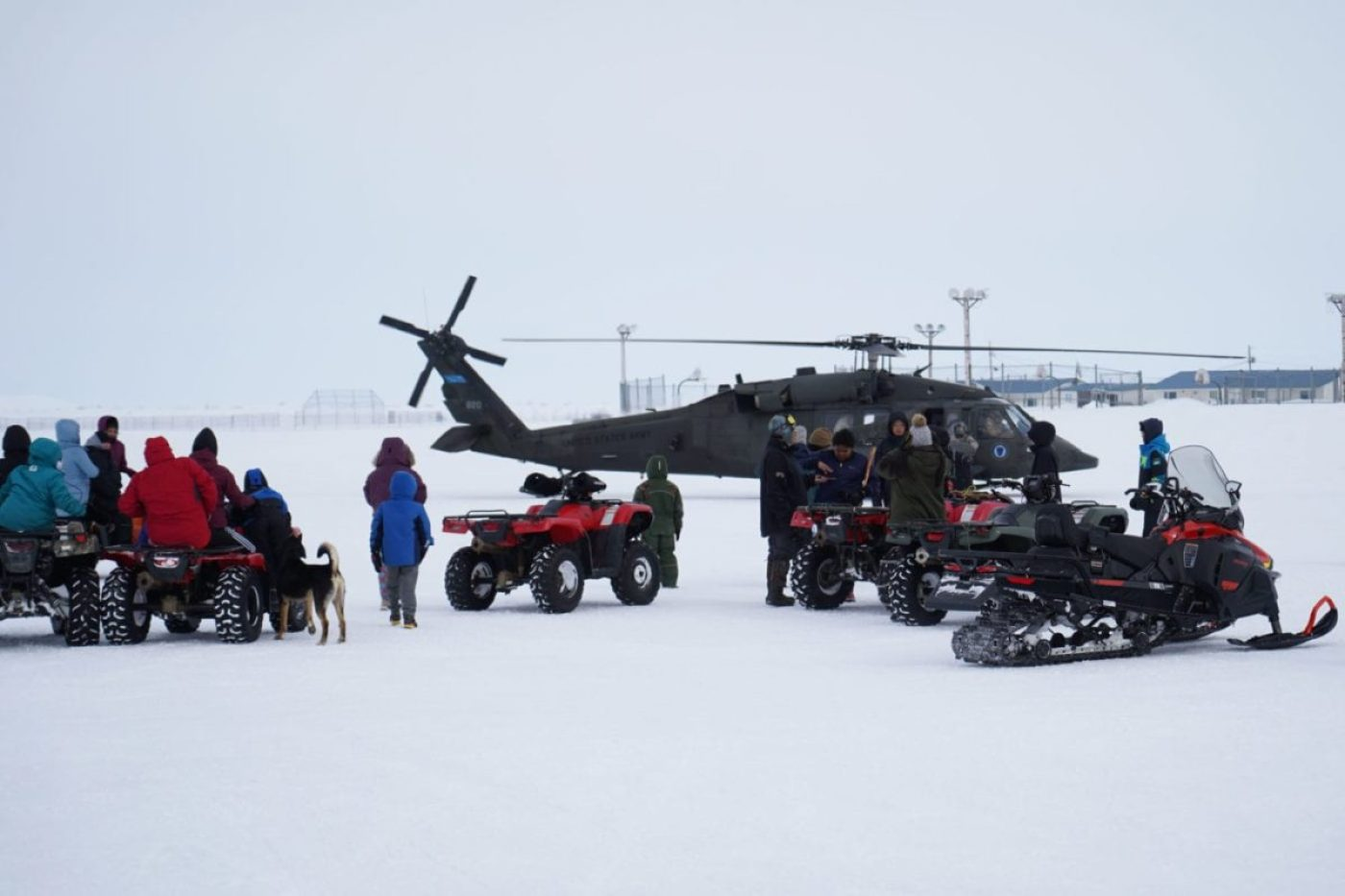 Community members of the city of Chevak, watch from a safe distance as representatives from the Alaska Department of Military and Veterans Affairs, the Department of Environmental Conservation and the Department of Commerce, Community and Economic Development load onto an Alaska Army National Guard UH-60 Black Hawk helicopter in Chevak, Alaska, April 9, 2021. Members of the Alaska Department of Military and Veterans Affairs, the Department of Environmental Conservation and the Department of Commerce, Community and Economic Development traveled to western Alaska April 7-9 to meet with tribal leaders and citizens in Bethel, Tuluksak and Chevak to discuss disaster assistance measures and processes in light of recent emergencies that have occurred in the region, and in preparation for the upcoming flood season. (U.S. Army National Guard photo by Dana Rosso)