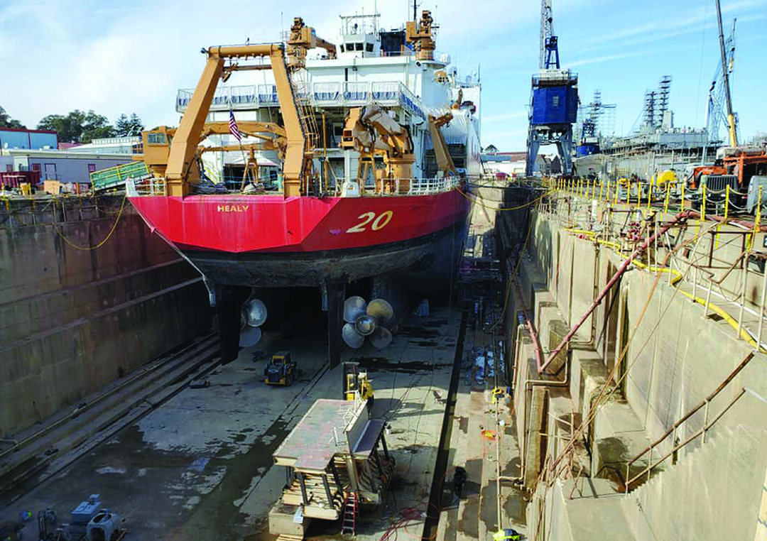 Healy in drydock at Mare Island to have the ruined propulsion motor replaced. The hull section cut out to enable the motor to be removed and replaced sits on the drydock floor behind the starboard propeller. (U.S. Coast Guard photo)