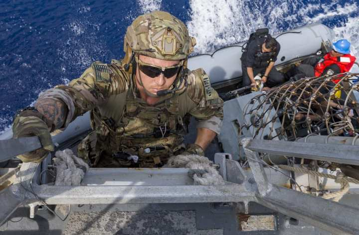 A member of a U.S. Coast Guard law enforcement detachment climbs down to a rigid-hull inflatable boat during an Oceania Maritime Security Initiative (OMSI) boarding mission. The OMSI program is a secretary of defense program leveraging Department of Defense assets transiting the region to increase the Coast Guard's maritime domain awareness, ultimately supporting its maritime law enforcement operations in Oceania. (U.S. Navy photo by Mass Communication Specialist 3rd Class Jasen Morenogarcia/Released)