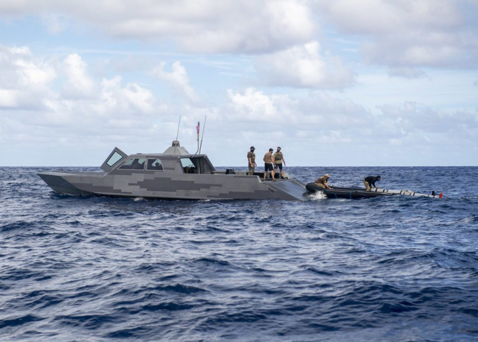 Sailors deployed with the expeditionary mine countermeasures (ExMCM) capability of Task Force 75 and Special Warfare Combatant Crewmen assigned to Special Boat Team 12 recover a MK 18 Mod 2 unmanned underwater vehicle (UUV) onto a Combatant Craft Medium (CCM) in Pago Bay, Guam. (U.S. NAVY PHOTO BY MASS COMMUNICATIONS SPECIALIST 1ST CLASS ADAM BROCK)