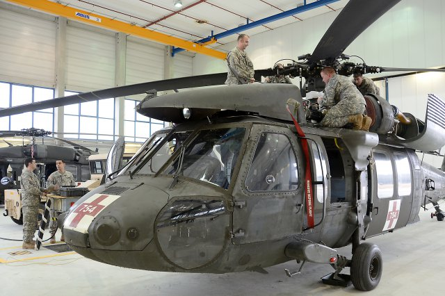 Soldiers from Landstuhl-based Company C, 1st Battalion, 214th Aviation Regiment conduct maintenance on a UH-60 Black Hawk helicopter used for medical evacuations.