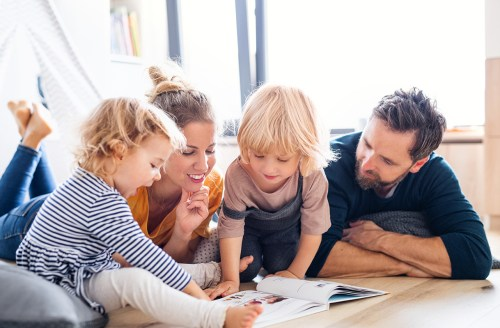 A family gathered on the floor around a book, reading together with warmth and comfort.