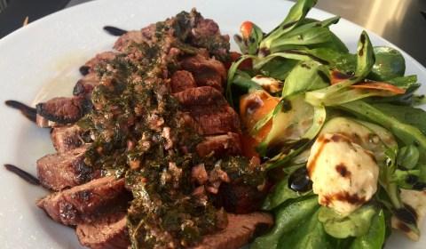 Rindersteakhüfte mit Chimichurri Sauce und Salat anrichten