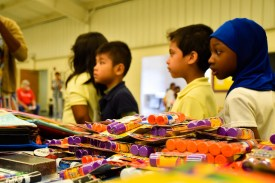 students look at school supplies on table