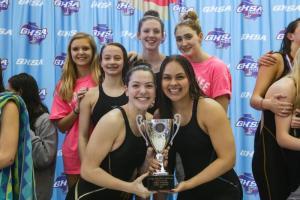 swim team holds championship trophy