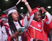 two students turn tassel