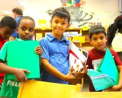 3 students hold school supplies