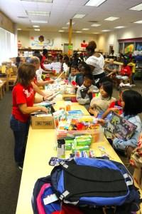 students recieve school supplies from volunteer