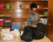 woman puts food in backpacks