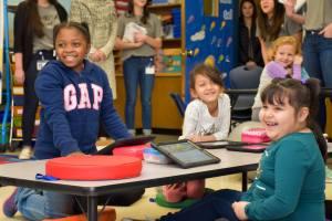 elementary school children in class smiling