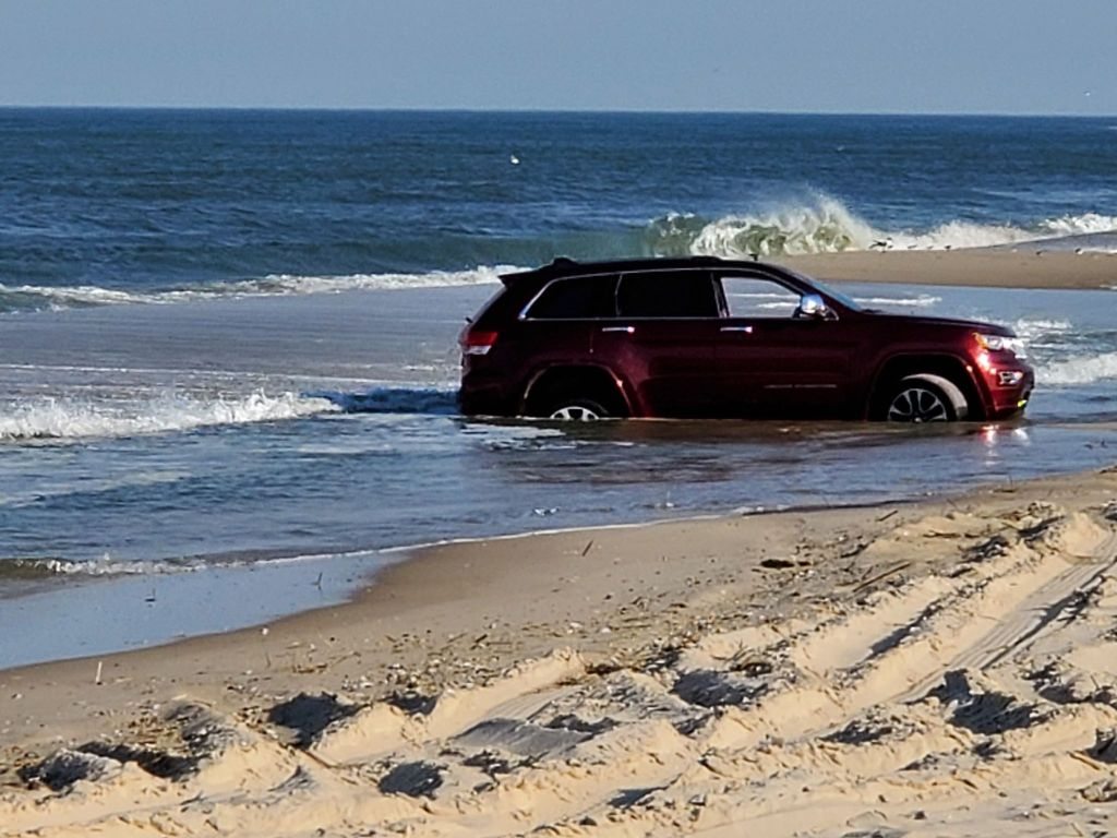 vehicle stuck in the swale or tide pool at coin beach in Delaware Seashore State Park